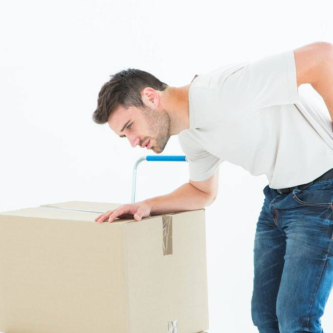 Upset delivery man with cardboard box suffering from backache on white background