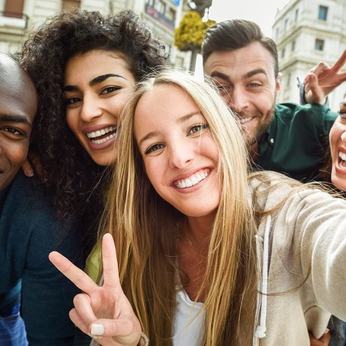 Multiracial group of friends taking selfie in a urban street with a blonde woman in foreground. Three young women and two men wearing casual clothes.